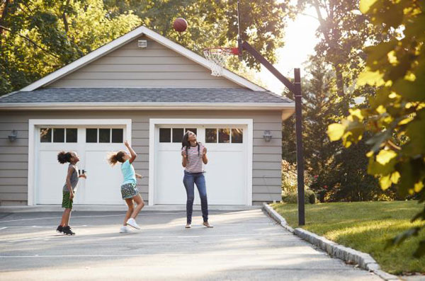 family enjoying basketball in front of 20x24 garage 0